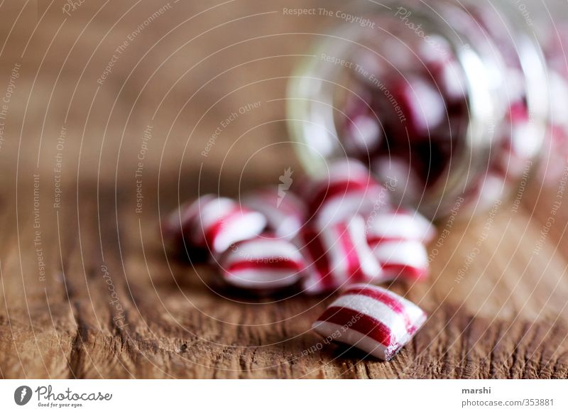 gestreiftes Süßes Lebensmittel Ernährung Essen rot weiß Bonbon Schwache Tiefenschärfe Glas Holztisch lecker Kalorie Süßwaren lutschen Streifen geschmackvoll