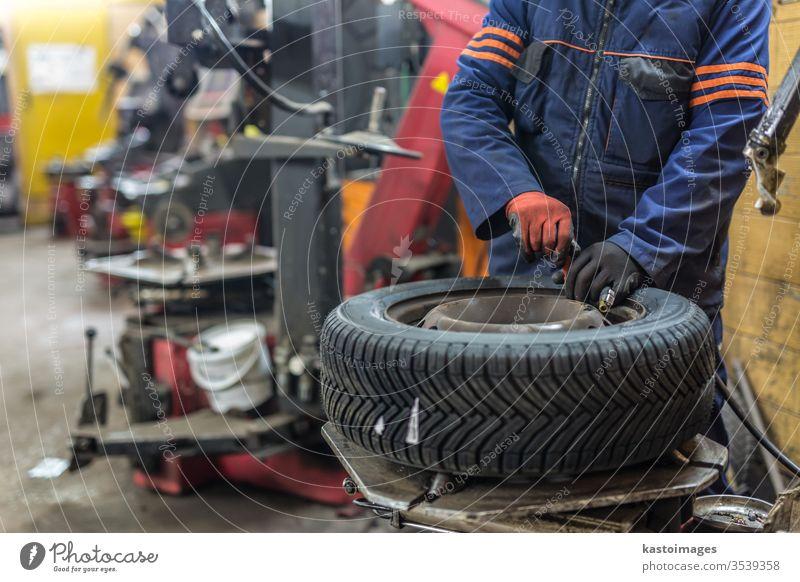 Professioneller Automechaniker beim Reifenwechsel im Autoreparaturdienst. Mechaniker Flugzeugwartung Ersatz Werkstatt Reparatur PKW Arbeiter Dienst fixieren Rad