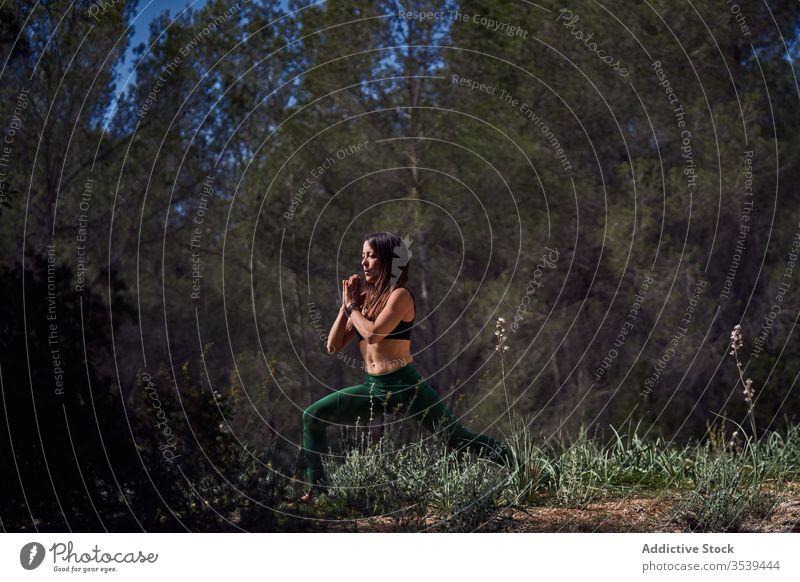 Junge Sportlerin beim Aufwärmen während eines Frontalausfalls an einem sonnigen Tag im Park Frau Athlet Ausfallschritt Dehnung Gleichgewicht Natur Übung
