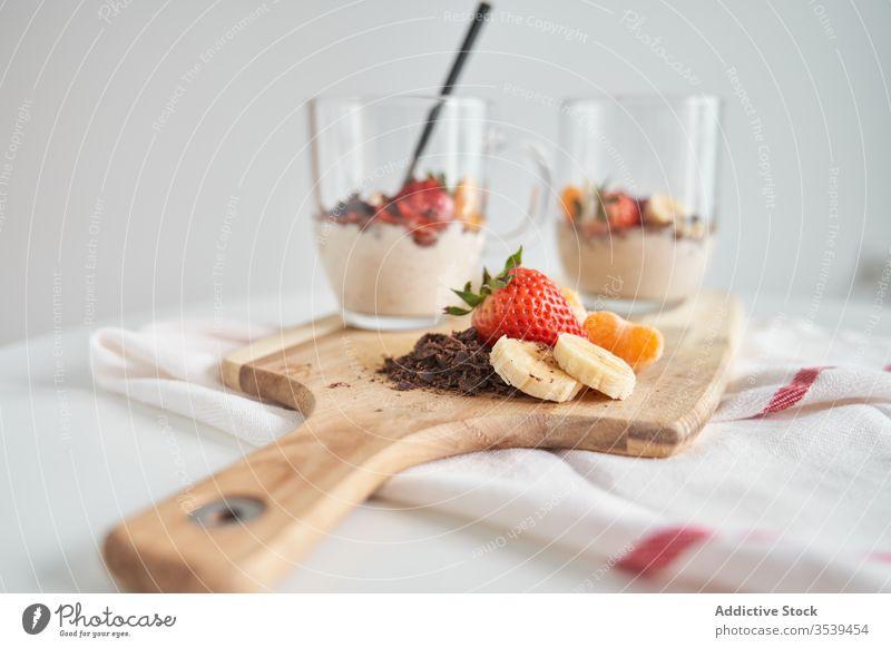 Becher Joghurt mit Früchten Frucht Tasse Frühstück Morgen Dessert Erdbeeren Mandarine Banane Schokolade frisch lecker Glas Schneidebrett hölzern Lebensmittel
