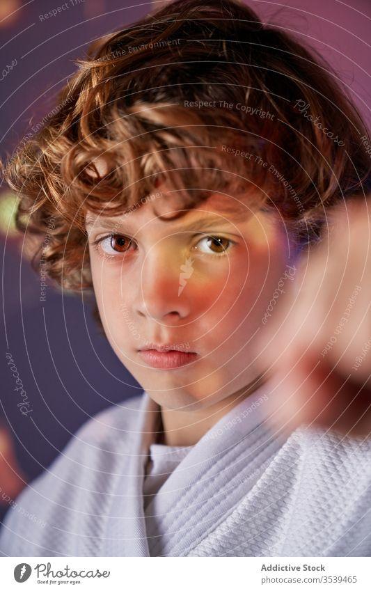Wütender Junge im Kimono beim Judo-Training im hellen Raum wütend Kick Kämpfer kämpferisch Kunst Bestimmen Sie attackieren Bowle üben Faust kämpfen Sport