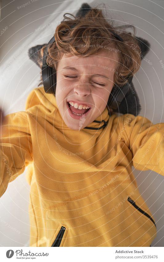 Zufriedenes Kind mit Kopfhörern auf dem Tisch liegend und Musik in hellem, modernem Raum genießend Junge Kälte zuhören heimwärts Glück Gesang Freude