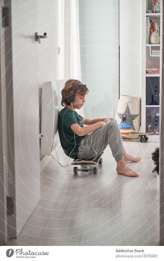 Kleines Kind in Kopfhörern mit digitalem Tablet beim Faulenzen zu Hause Junge Tablette Spiel heimwärts Skateboard spielen Musik Video benutzend räkeln zuschauen
