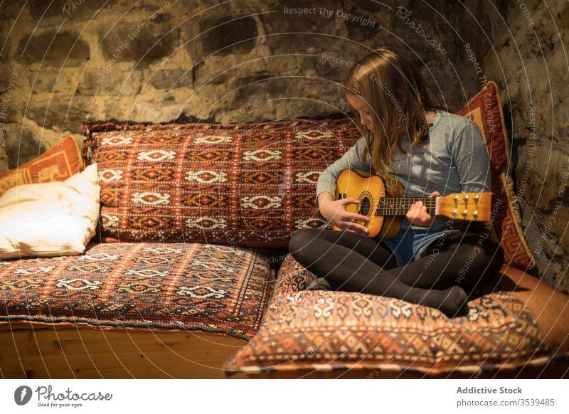 Ukulele spielendes Mädchen auf der Couch in einem Steinhaus während eines Urlaubs in Spanien Liege Haus Land üben Sofa Musik Komfort gemütlich Kantabrien