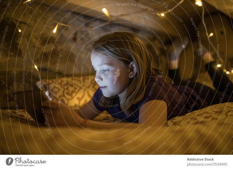 Zufriedenes Mädchen benutzt Tablette, während sie auf einem mit einer Girlande geschmückten Bett ruht Browsen Nacht gemütlich Windstille glühen leuchten Komfort