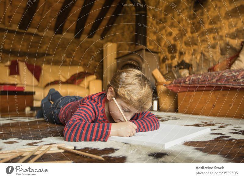 Kinderzeichnung mit Farbstiften im Skizzenbuch im Wohnzimmer Junge Haus Land Kabine Inspiration Natur jung Zeichnung Teppich Spanien Kantabrien Stein zeichnen
