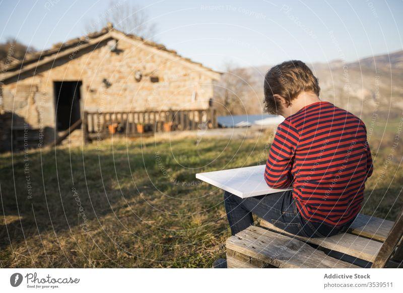 Junge zeichnet, während er auf einer Bank in einem Dorf im Hochland sitzt zeichnen Leinwand Inspiration Kunst Farbe Berge u. Gebirge Hobby Kind Landschaft