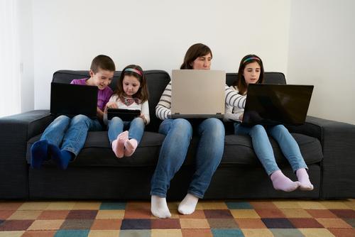Seriöse Mutter und Kinder verbringen zu Hause Zeit miteinander, indem sie Gadgets auf dem Sofa benutzen Laptop beschäftigt Süchtige benutzend heimwärts
