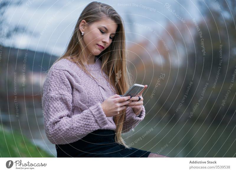 Lächelnde Frau surft auf einem Smartphone, während sie sich bei Sonnenuntergang im Park ausruht Browsen ruhen Glück heiter froh benutzend zuschauend