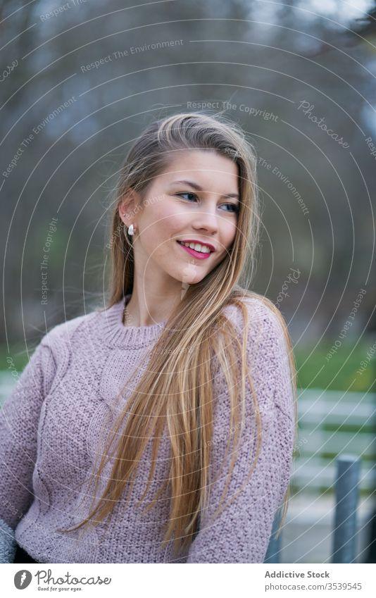 Positive junge Studentin mit wallendem Haar im Park Frau Lächeln Individualität Art positiv Stimmung Persönlichkeit Porträt Glück Spaziergang Pflege verträumt
