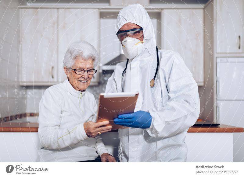 Medizinischer Spezialist erklärt älteren Patienten während der Quarantäne die Verschreibung Coronavirus Senior Tablette heimwärts Arzt geduldig Pflege