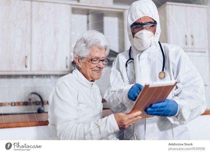 Medizinischer Spezialist erklärt älteren Patienten während der Quarantäne die Verschreibung Coronavirus Tablette Senior heimwärts Arzt geduldig Pflege
