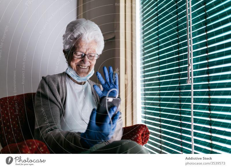 Fröhliche ältere Frau plaudert während der Selbstisolation zu Hause am Smartphone Aufenthalt heimwärts Coronavirus Senior Fenster benutzend heiter Kommunizieren