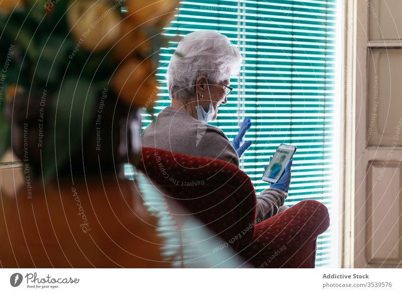 Alte Frau bei Videogesprächen auf Smartphone zu Hause Aufenthalt heimwärts Coronavirus Senior Videoanruf benutzend heiter Kommunizieren gestikulieren Gruß