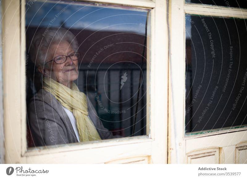 Ältere Frau schaut aus dem Fenster Senior Coronavirus heimwärts einsam Anspannung verzweifelt unglücklich traurig Quarantäne verhindern alt behüten allein