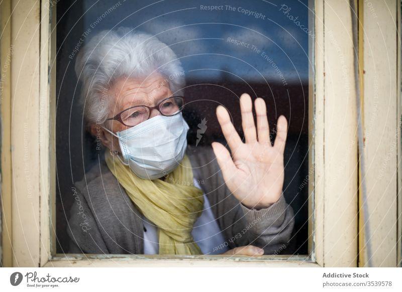 Ältere Frau mit Schutzmaske, die aus dem Fenster schaut Senior Coronavirus Mundschutz heimwärts einsam Anspannung verzweifelt unglücklich traurig Quarantäne