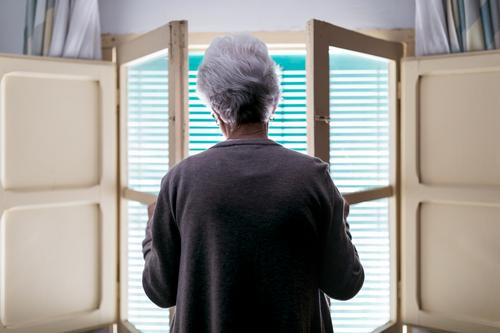 Grauhaarige Frau steht zu Hause vor dem Fenster heimwärts Senior einsam Quarantäne Coronavirus Fensterladen offen allein alt Einsamkeit Konzept gealtert