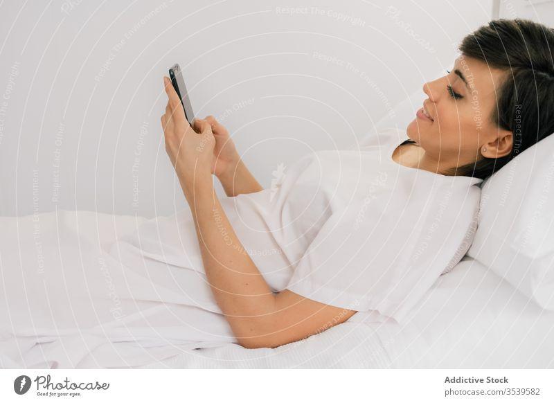 Glückliche Patientin mit Smartphone auf der Krankenhausstation Frau geduldig Station liegend benutzend Lächeln Stuhl Bett modern Robe heiter weiß Browsen Klinik