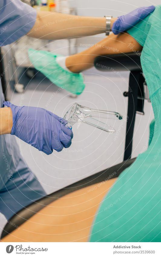 Anonymer Gynäkologe mit gynäkologischem Spiegel untersucht nicht erkennbare Patientin in der Klinik Frauenarzt untersuchen geduldig steril Handschuhe Stuhl