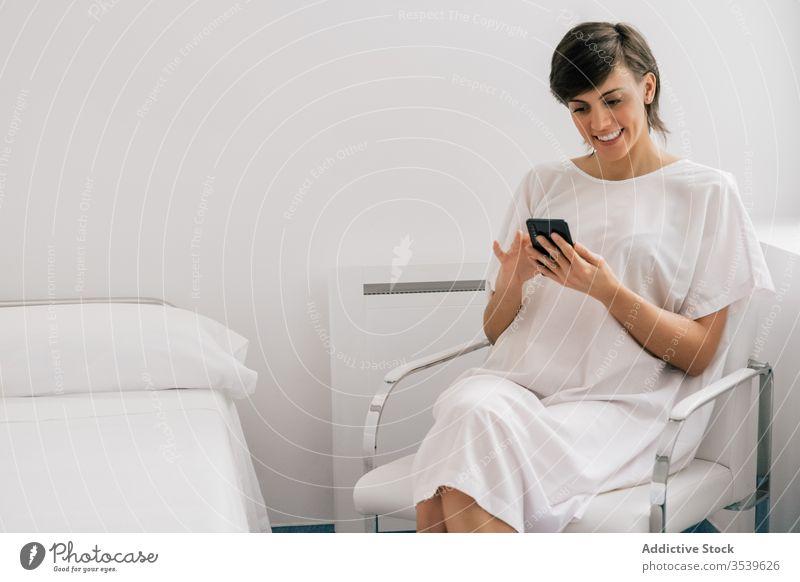 Glückliche Patientin mit Smartphone auf der Krankenhausstation Frau geduldig Station benutzend Lächeln Stuhl sitzen Bett modern Robe heiter weiß Browsen Klinik