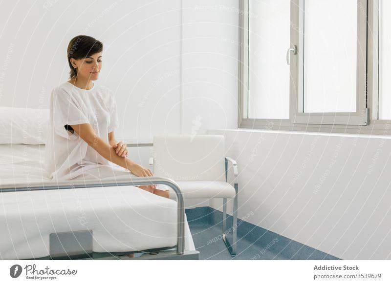 Positive Patientin sitzt im Krankenhaus auf dem Bett Frau geduldig Station positiv Robe modern Licht weiß froh Freude Klinik Glück ruhen sich[Akk] entspannen