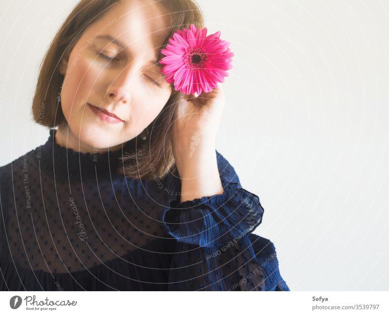 Wunderschönes weibliches Porträt mit rosa Gerbera-Blüte Frau Blume Schönheit Muttertag Mode eine einzigartig Haut Auge Pflege Gesicht jung Hand Beteiligung