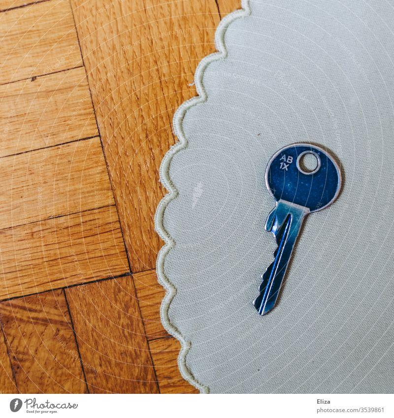 Ein blauer Schlüssel auf einem Stoffdeckchen auf Holz wohnen Hausschlüssel Sicherheit Innenaufnahme Tag zuhause Wohnung