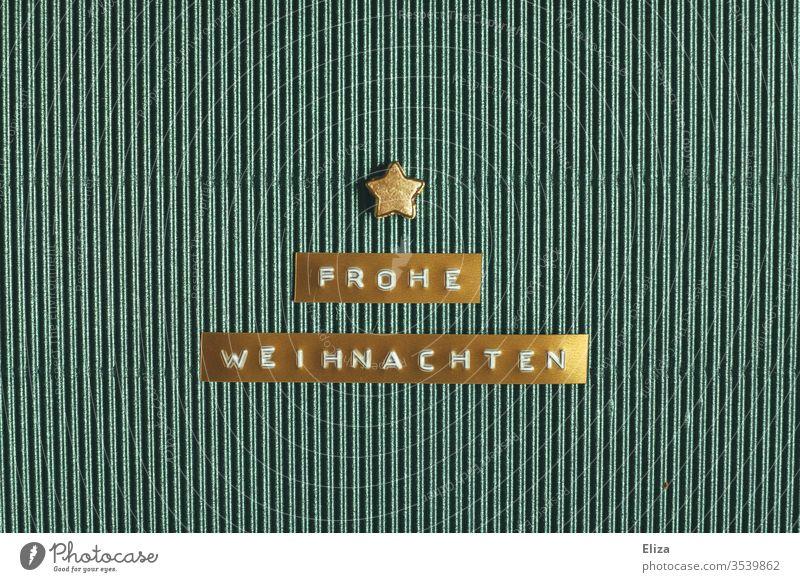 Goldenes Etikett auf dem Frohe Weihnachten steht mit einem goldenen Stern auf türkiser Wellpappe geschrieben Weihnachtsgruß Weihnachtskarte Text Worte