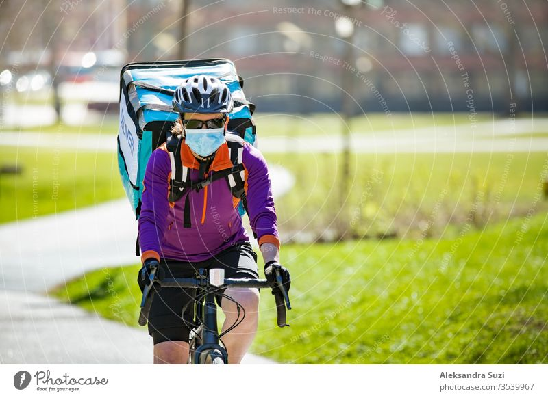 Frau mit Helm und Schutzmaske mit großem Essenslieferungsrucksack mit Fahrrad auf der Straße. Sonniger Frühlingstag in der Stadt. Porträt eines weiblichen Kuriers in einer medizinischen Maske.