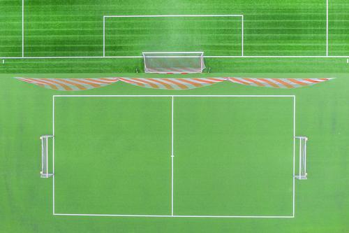 ein grünes leeres Fußballfeld von oben Fußballfeldtor Fußballtor Linien Sport Sportplatz kleiner Fußballplatz Gras Sonne Schatten Laufbahn rennen Aschefeld
