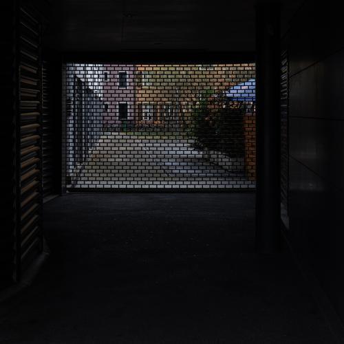 Ein dunkler Zugang zu einem Hinterhof ist durch ein Rollgitter abgesperrt, hinter dem Rollgitter farbige Fassaden des Hinterhofes rollgitter Hausdurchgang