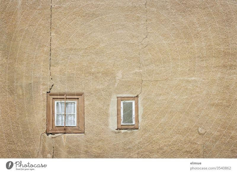 zwei winzige, ganze Holzfenster in einer sandfarbenen Wand mit Rissen Fenster marode Gardine Verfall Spekulationsobjekt Ausblick baufällig Altbauwohnung Putz