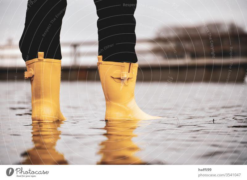 gelbe Gummistiefel stehen auf der überfluteten Promenade Hochwasser Klimawandel Überflutet hochwasserlage Umwelt globale Erwärmung Weser Meer Wasser Landschaft