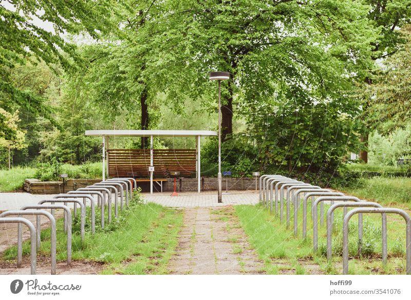"leere Fahrradständer im Hof umringt von üppigem Grün grün ""Fahrradständer Fahrradhalter Fahrradparkplatz Radständer Parkplatz parkraum stellplatz fahrradständer"