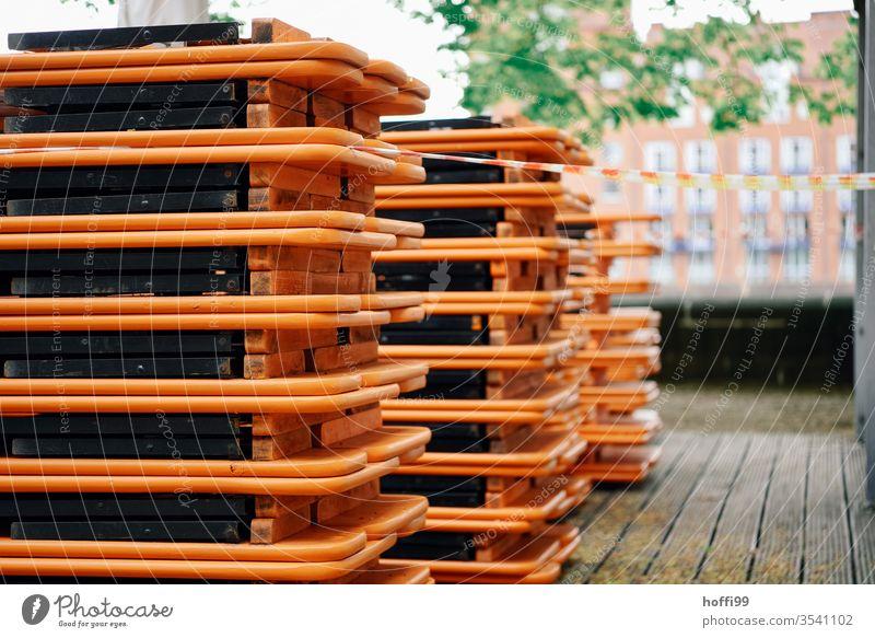 gestapelte Bierzeltgarnituren auf einer Aussenterrasse covid-19 Lockdown Ausgehsperre Beschränkung Herbst biergartensaison biergartengarnitur Biergarten