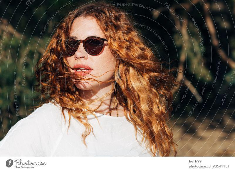 junge Frau mit Sonnenbrille und roten lockigen Haaren dreht sich der Sonne entgegen rote Haare rote lippen Locken lockiges haar rothaarig rote Lippen schön