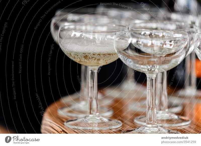 Sekt, Champagner in Gläsern auf dem Holztisch auf schwarzem Hintergrund im Restaurant. Glas Hand Kellnerin Catering Menschengruppe Handschuhe offen Party Person
