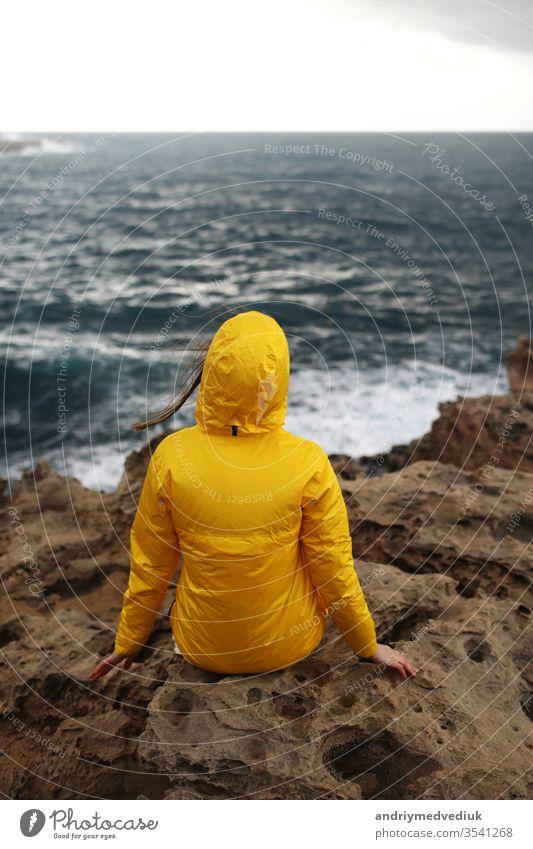 junge Frau im gelben Regenmantel auf der Klippe sitzend und auf die großen Wellen des Meeres schauend, während sie an einem Regentag am Felsstrand bei bewölktem Frühlingswetter die schöne Meereslandschaft genießt