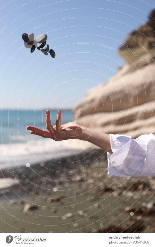 weibliche Hand wirft einen Kieselstein in die Hand vor dem Hintergrund des blauen Himmels, des Strandes, der Felsen und des Meeres. Frau MEER Mädchen
