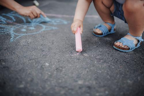 Nahaufnahme einer Zeichnung eines kleinen Mädchens mit Kreiden auf dem Bürgersteig Farbe Hand Straßenbelag wenig Kunst Sommer Hintergrund farbenfroh Spaß