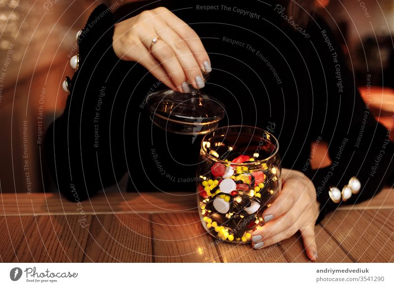 junge Frau zeigt Flasche mit Medikament. farbige Kapseln. Verschiedene medizinische Kapseln, die aus einem Glas ausgelaufen sind. medizinisches Konzept Medizin