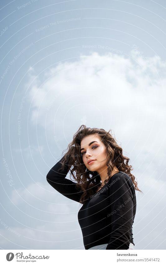 Bildnis einer jungen erwachsenen weißen Frau vor blauem Himmel, selektiver Fokus Kaukasier Freiheit krause Haare brünett Frühling allein attraktiv Mädchen
