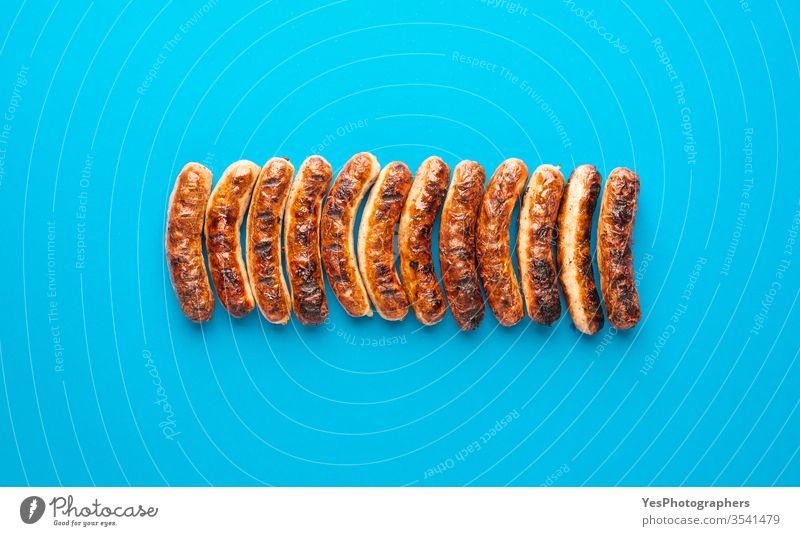 Gegrillte Nürnberger Bratwurst. Deutsche Würstchen Draufsicht obere Ansicht authentisch Barbecue Bayern bayerisch grillen Blauer Hintergrund braun Weihnachten