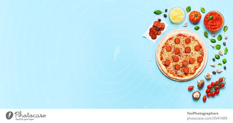 Herstellung von Pizza-Peperoni mit rohem Teig und Zutaten Italienisch Kunstgewerbler zu Hause authentisch Transparente Blauer Hintergrund Käse Essen zubereiten