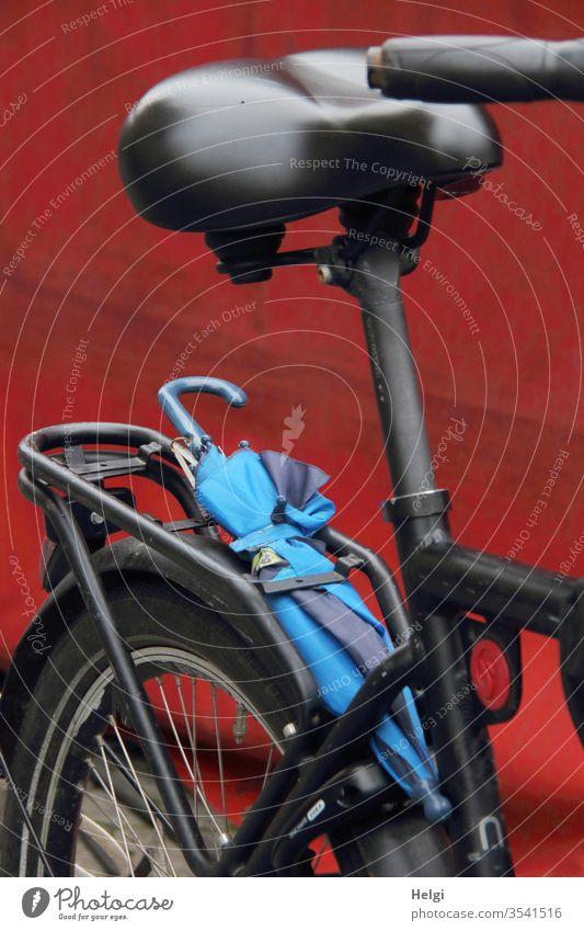 es könnte Regen geben - Detailaufnahme eines schwarzen Fahrrades mit blauem Regenschirm, der  auf dem Gepäckträger klemmt Verkehr Niederlande Fahrradfahren