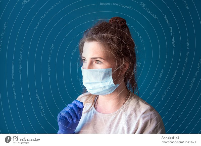 Junge Frau trägt Schutzhandschuhe und Gesichtsmaske in einem Haus in Quarantäne und sieht gelangweilt und traurig aus, für Covid-19 Coronavirus, mit blauem Hintergrund