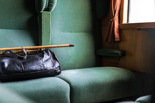 Der Sitz neben der schwarzen Tasche und dem Gehstock ist noch frei Antiquität Gepäck Holzplatte Kabine bequem Fach Design leer Erste Klasse Möbel grün