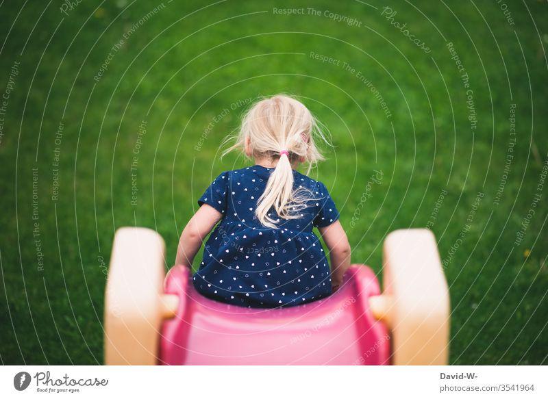 Kind rutsch die Rutsche hinunter Mädchen rutschen rutscht Garten Spielen draußen Natur Rückansicht Kindheit Freizeit & Hobby Freude Farbfoto Tag Kleinkind