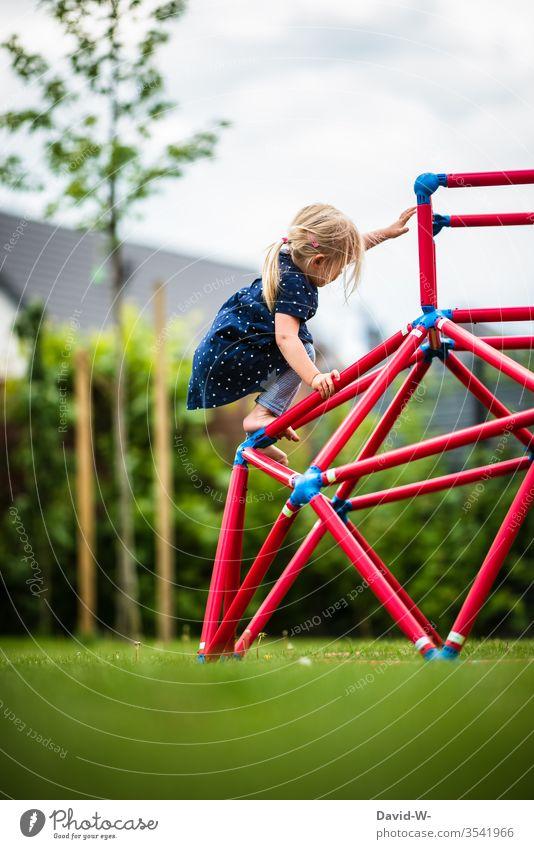Mädchen klettert auf einem Klettergerüst im Garten klettern Spaß freude mutig Kinder kindlich niedlich spielen beschäftigung Gartenspielzeug spielend greifen