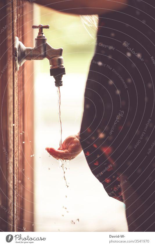 Kind fängt Wasser aus dem Wasserhahn mit der Hand auf Finger fühlen Wassertropfen neugierig sommer sommerlich draußen nass Tropfen Garten grün Sommer